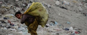 Image: A young Afghani garbage collector carries recyclable material from a landfill
