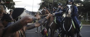 Police confront native Brazilians to impede them from marching towards the Mane Garrincha soccer stadium during a demonstration in Brasilia